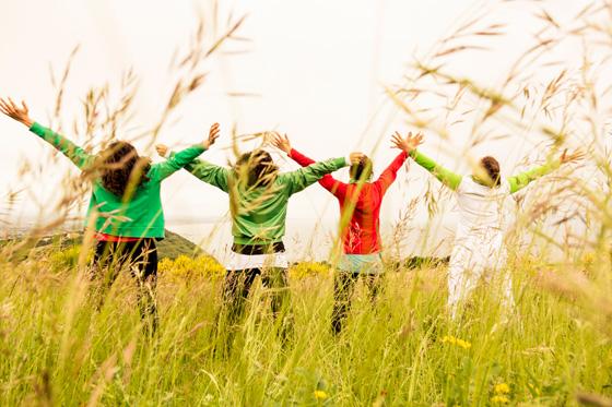 Women doing yoga in field